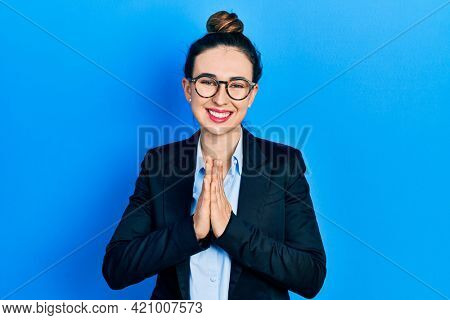 Young hispanic girl wearing business clothes and glasses praying with hands together asking for forgiveness smiling confident.