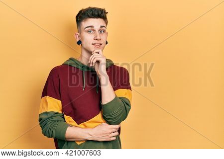 Young caucasian boy with ears dilation wearing casual sweatshirt looking confident at the camera with smile with crossed arms and hand raised on chin. thinking positive.