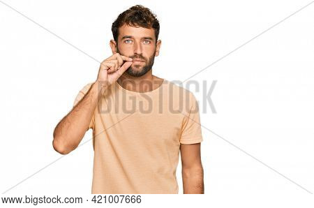 Handsome young man with beard wearing casual tshirt mouth and lips shut as zip with fingers. secret and silent, taboo talking