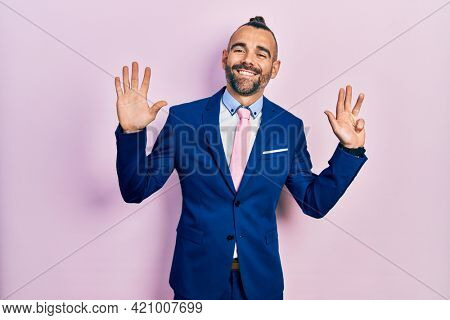 Young hispanic man wearing business suit and tie showing and pointing up with fingers number nine while smiling confident and happy.