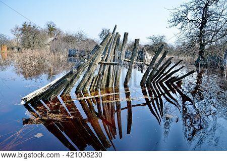 Belarus. Petrikov - April 2013: Flooding In A Village. Flooded Fence In Spring, Flood.