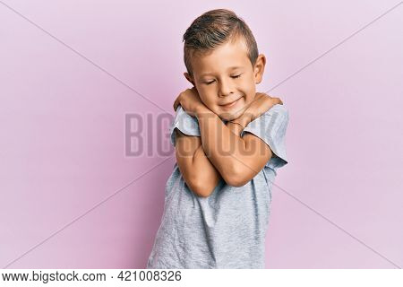 Adorable caucasian kid wearing casual clothes hugging oneself happy and positive, smiling confident. self love and self care