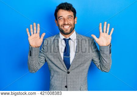 Handsome man with beard wearing business suit and tie showing and pointing up with fingers number ten while smiling confident and happy.