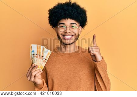 Young african american man with afro hair holding 500 philippine peso banknotes smiling with an idea or question pointing finger with happy face, number one
