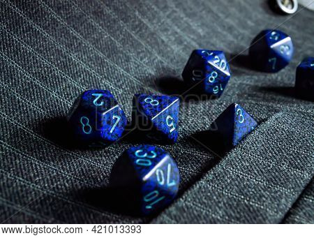 Close-up Of A Set Of Blue Role-playing Game Dice On A Pinstriped Grey Vest