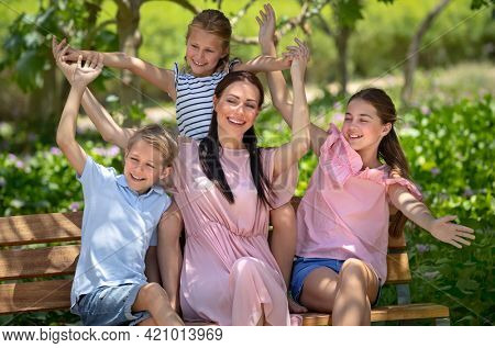 Happy Mother and Her Three Precious Kids Sitting on the Bench in the Park. Big Family Having Time and Joking in City Park on Summer Day. Love Concept.
