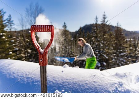 Selective Focus. Red Shovel Handle In Foreground. In The Blurred Background, A Young Man Removing Kn