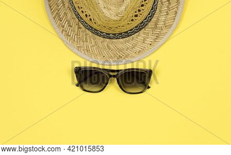 Summer Background. Straw Sun Hat And Sunglasses On A Yellow Background. Top View, Close-up, Horizont