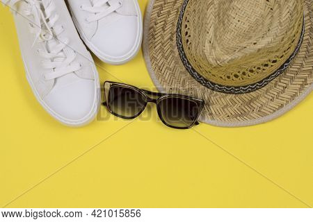 Summer Background. Straw Sun Hat, Sunglasses And White Sneakers On A Yellow Background. Top View, Cl