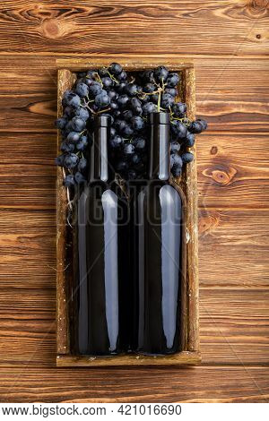 Two Red Wine Bottles Composition On Brown Wooden Table. Red Wine Bottles In Box On Black Ripe Grapes
