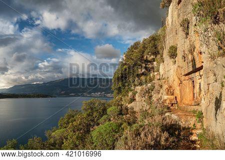 Ancient rock-cut Lycian tombs near Kas town on a Lycian way trekking route along the Mediterranean coast in Turkey