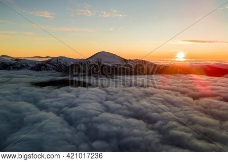 Aerial View Of Vibrant Sunrise Over White Dense Clouds With Distant Dark Mountains On Horizon.