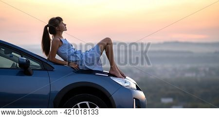 Young Female Driver Resting On Hood Of Her Car Enjoying Warm Summer Evening. Travel And Getaway Conc