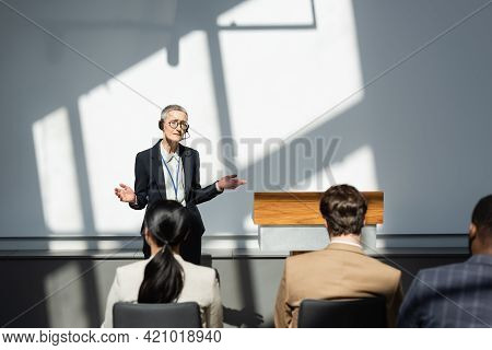 Confused Lecturer Showing Shrug Gesture In Front Of Blurred Participants During Seminar.