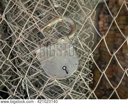An Old Padlock Is Hanging From A Barbed Wire With Cobwebs In An Open State. Conception Of The Need T