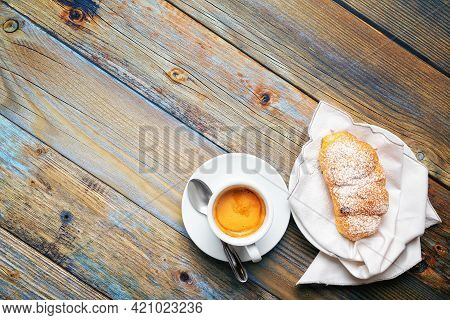Cup Of Espresso Coffee And Brioche On An Old Wooden Table.