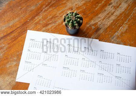 Desktop Calendar And Cactus Placed On Student Wooden Desk In Garden, Calender For Planner To Plan Da