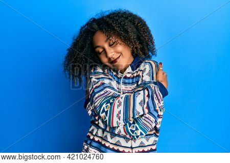 Beautiful african american woman with afro hair wearing casual clothes hugging oneself happy and positive, smiling confident. self love and self care