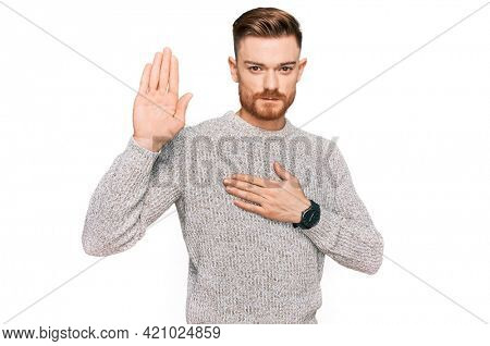 Young redhead man wearing casual winter sweater swearing with hand on chest and open palm, making a loyalty promise oath