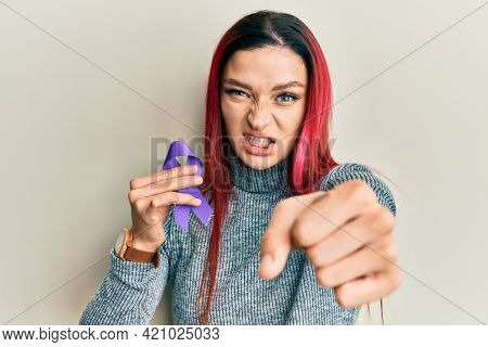 Young caucasian woman holding purple ribbon awareness annoyed and frustrated shouting with anger, yelling crazy with anger and hand raised