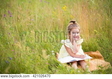 Girl In A Yellow Dress Sits In The Grass On A Blanket In A Field And Reads A Paper Book. Internation
