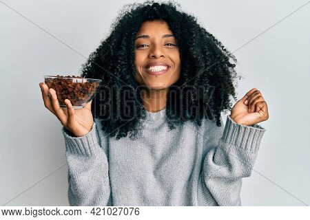 African american woman with afro hair holding raisins in bowl screaming proud, celebrating victory and success very excited with raised arm