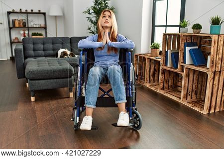 Young beautiful woman sitting on wheelchair at home begging and praying with hands together with hope expression on face very emotional and worried. begging.