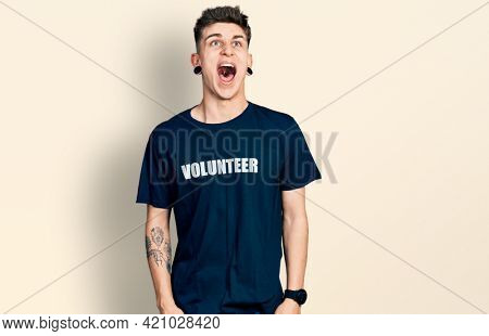 Young caucasian boy with ears dilation wearing volunteer t shirt angry and mad screaming frustrated and furious, shouting with anger. rage and aggressive concept.