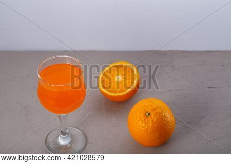 Orange Juice In A Glass Near Oranges On A Gray Background. Horizontal Photo