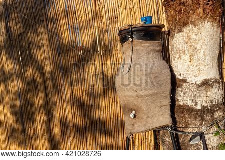 Public Earthenware Jug With Drinking Water Hidden In A Mat And With A Plastic Mug On A Rope Tied On