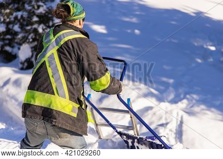 Rear View Of A Young Man In Visibility Jacket And Blue Manual Shovel Removing Knee Deep Fresh Snow F