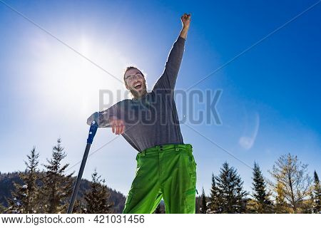 Funny, Arm Up Portrait Of A Smiling Man Leaning On The Handle Of A Blue Snow Shovel While Taking A B