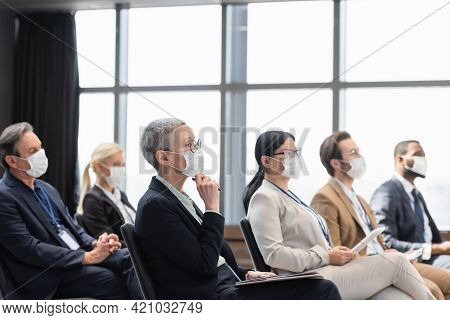 Multiethnic Business People In Medical Masks Sitting In Conference Room During Conference.