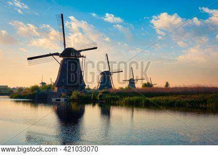 Netherlands rural lanscape with windmills at famous tourist site Kinderdijk in Holland on sunset with dramatic sky