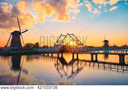 Netherlands rural lanscape with windmills and bridge at famous tourist site Kinderdijk in Holland on sunset with dramatic sky