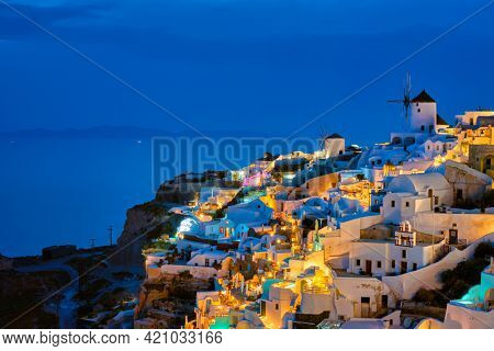 Famous greek iconic picturesque tourist destination Oia village with traditional white houses and windmills in Santorini island in the evening blue hour, Greece