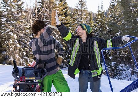 Portrait Of Two Young Men Doing A High Five And Posing With Their Snow Removing Tools, A Bright Oran