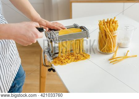 Man In Apron Making Spaghetti With Noodle Cutter. Close-up Pasta Cooking At Home. Preparing Food Fro