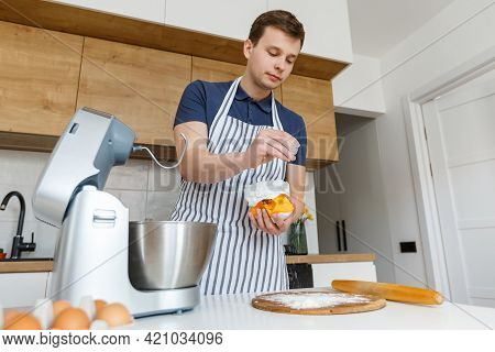 Young Handsome Man In Apron Sifting Flour In Modern Kitchen. Concept Of Homemade Bakery Food, Male C