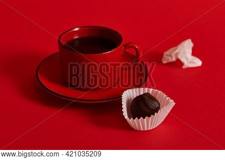 Closeup Of A Ceramic Coffee Cup With Coffee In A Red Saucer, Next To Chocolate Truffle And A Crumple