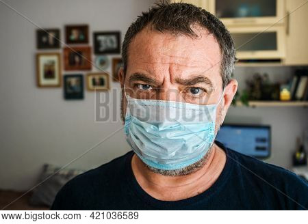 Sick sad mature man in protective medical mask at home in the room. COVID-19 pandemic, lockdown concept