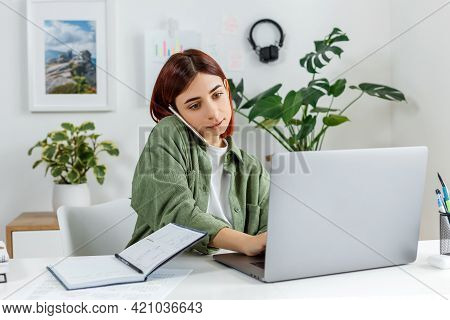 Woman Remotely Working At Home With Laptop Computer. Young Businesswoman Talking By Phone. Concept O