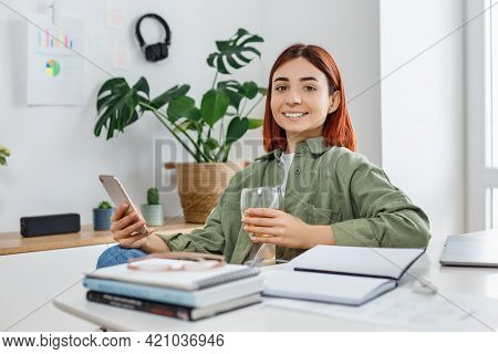 Woman Using Mobile Phone And Drinking Tea. Young Businesswoman At Comfortable Workplace. Concept Of