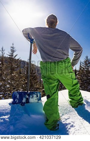 Close Up, Rear View Of A Young Man Leaning On The Handle Of A Blue Snow Shovel While Taking A Break