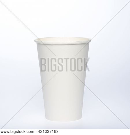 Photo of a disposable  white paper cup on a white background. Photo of a coffee cup made of recyclable materials. Empty paper coffee cup.