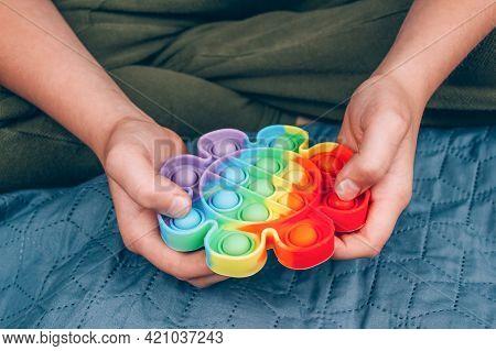 Autistic Boy Using Rainbow Pop It Fidget Toy. Push Bubble Fidget Sensory Toy - Washable And Reusable