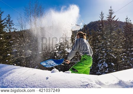 View From Behind Of A Young Man Energetically Removing Fresh Snow From A Roof With A Blue Hand Shove