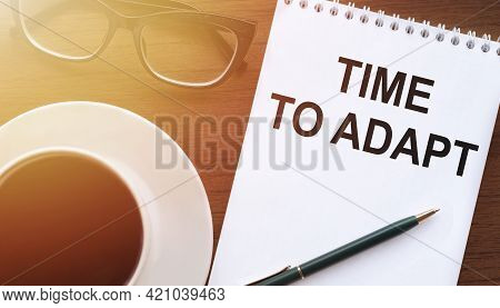 Time To Adapt - Text On Paper With Cup Of Coffee And Glasses On Wooden Background In Sinlight.