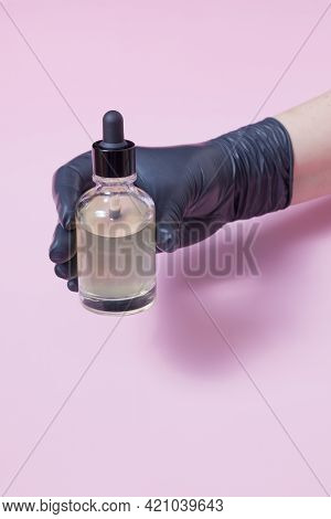 Famale Hand In A Black Medical Glove Holds A Glass Dropper Bottle With Cosmetic Oil On Color Backgro