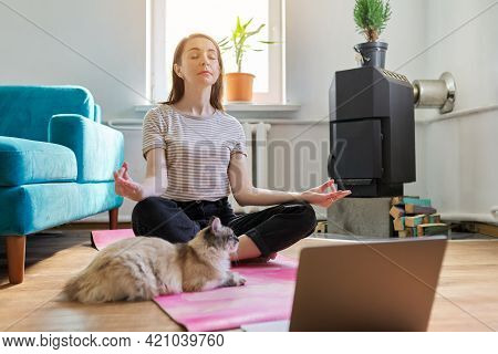 Middle Aged Woman Sitting At Home On Floor With Laptop In Lotus Position